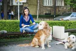 A young woman is sitting on a bench holding leashes to two large dogs with link to the article.