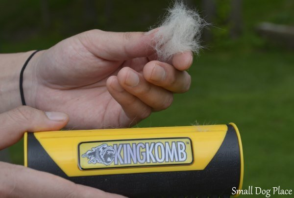 A man is holding a King Komb in one hand and a ball of dog hair in the other.