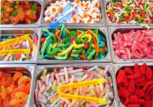 Nine different colorful candy assortment with tongs featured as a candy bar.
