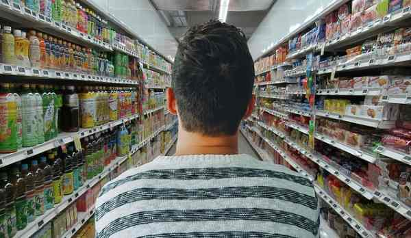 A man is entering an aisle in the grocery store.