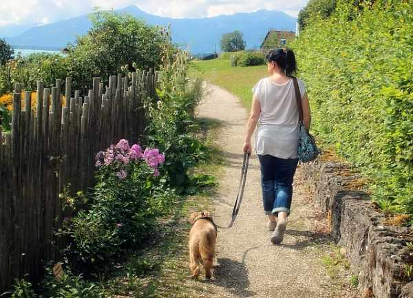 A young woman is walking her small dog down a dirt path.