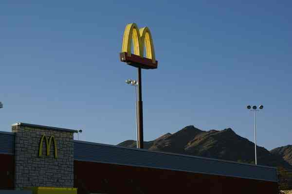 A picture of golden arches in front of the night sky.