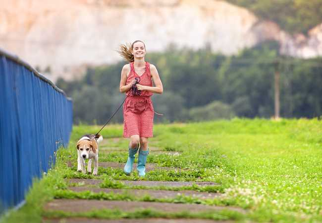 A girl is running with her small dog